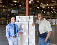 Warehouse employee and his boss posing for a portrait. The worker is leaning on a pallet of card board boxes, and the boss is standing next to the stack of boxes. The supervisor has a clipboard and his hand is in his pocket.